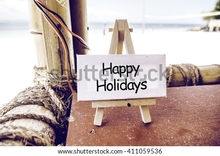Conceptual image, word HAPPY HOLIDAY on white canvas and easel.Bamboo hut with tropical beach background at sunny day. - stock photo