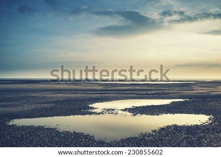 Conceptual landscape image of two people on remote beach with Instagram style filter - stock photo