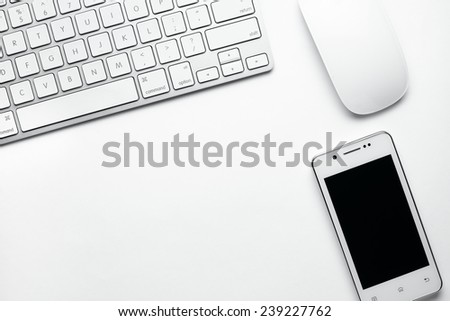 Conceptual Mobile Phone, White Computer Keyboard and Mouse on Table Top with Copy Space for Texts. - stock photo