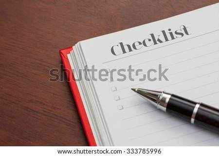 Conceptual,notebook on a wooden table. open diary and pen with checklist word - stock photo