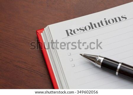 Conceptual,notebook on a wooden table. open diary and pen with resolutions word - stock photo