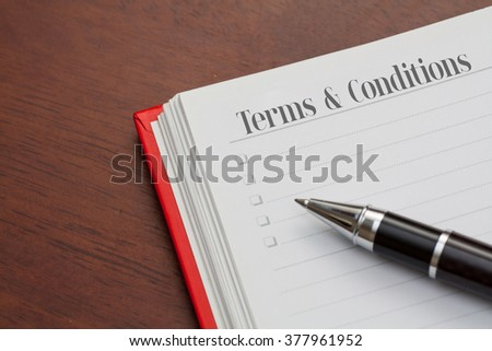 Conceptual,notebook on a wooden table. open diary and pen with Terms and Conditions words - stock photo