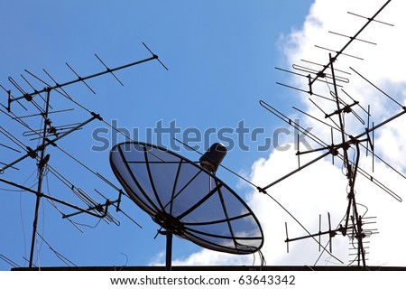 conceptual of satellite and antenna on blue sky - stock photo