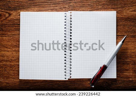 Conceptual Open Spiral Graphing Notebook and Pen on Brown Wooden Table with Copy Space for Texts. - stock photo