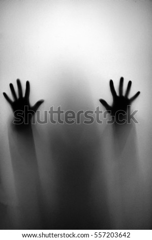Conceptual photo hand on the glass, silhouette through the glass, hand limbs through windows. Diffused silhouette through frosted glass