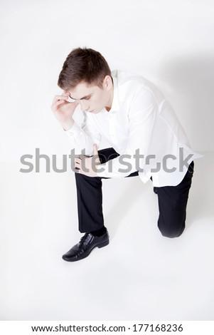 Conceptual photo of tired sad young businessman. Studio shot. - stock photo