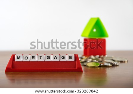 """Conceptual photo of word """"Mortgage"""" spelled by alphabet blocks arrangement. Selective focusing, shallow depth of field. - stock photo"""