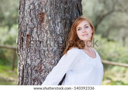 Conceptual portrait of fresh female leaning at the big trunk - stock photo