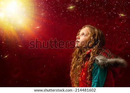 Conceptual portrait of girl staring at bright sun against reddish background.  - stock photo