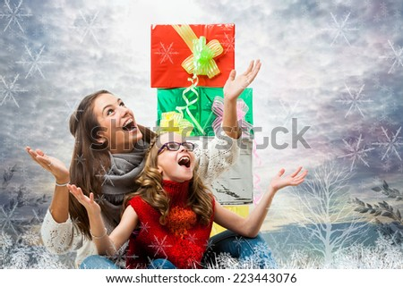 Conceptual portrait of happy girls at Christmas with arms open under snow. - stock photo