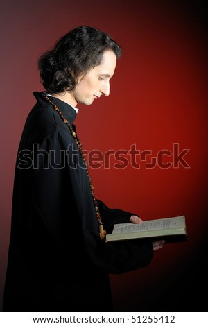 conceptual portrait of Praying priest with wooden cross reading Holy Bible. red background - stock photo