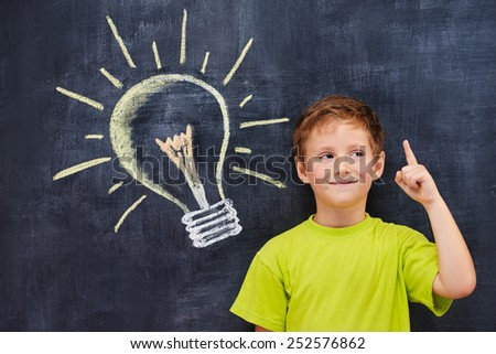 Conceptual portrait of redhead primary age school boy with pictured lightbulb - stock photo