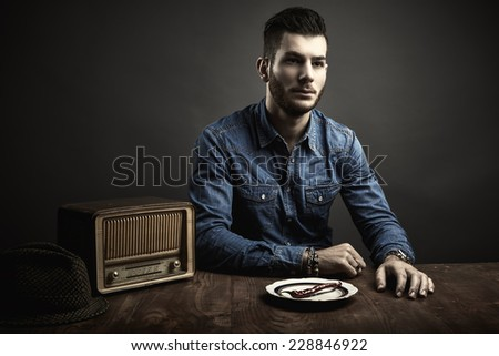 Conceptual portrait of young man sitting at a table, vintage style - stock photo
