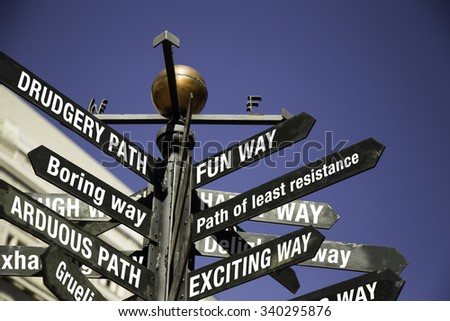 Conceptual sign post. Directional sign with messages, fun, exciting, path of least resistance in one direction, and Drudgery Path, Boring, Arduous on other directions.  - stock photo