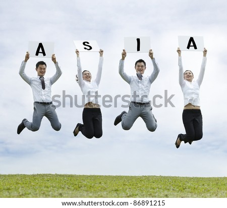 Conceptual Stock image of an Asian man & woman jumping holding sign - stock photo
