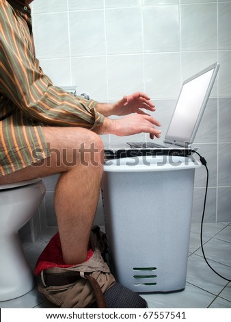 """Conceptual view of  an internet addict during """"calling of nature""""  in the toilet. - stock photo"""