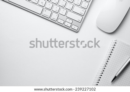 Conceptual White Ballpoint Pen, Clean Spiral Notes, Computer Keyboard and Mouse on Top of White Table with Copy Space at the Center.