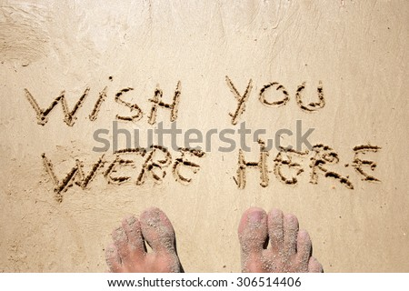 Conceptual wish you were here text handwritten in sand on a beach with feet in an exotic island for tropical, summer, sea, ocean, calendar, travel, holiday, sunny, tourism, resort, time, relax - stock photo