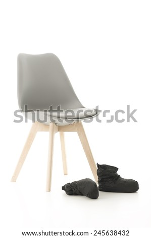 Conceptual Wooden Leg Chair and Black Boots Isolated on White Background. - stock photo