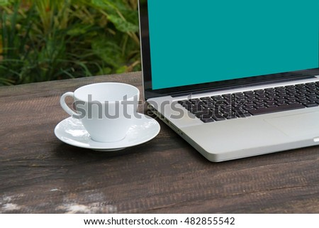 Conceptual workspace, Laptop with blank screen on table,coffee cup and green garden background,business technology concept