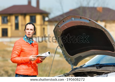 Concerned about the girl in the broken car with open hood User Guide - stock photo