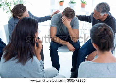 Concerned patients comforting another in rehab group at a therapy session - stock photo