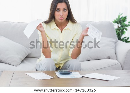 Concerned woman doing her accounts sat on a couch - stock photo