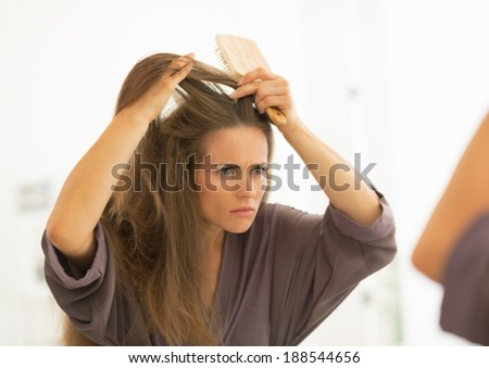 Concerned young woman combing hair in bathroom - stock photo