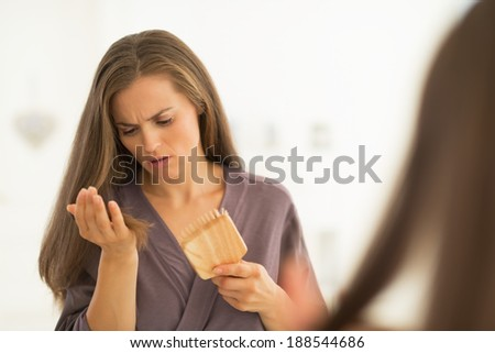 Concerned young woman looking on hair comb after combing