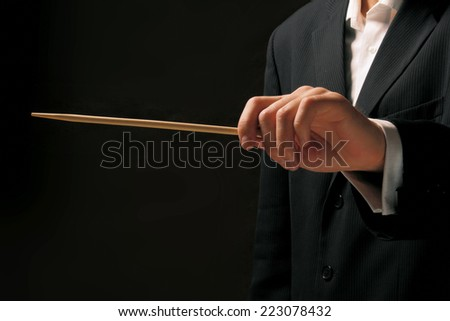 Concert conductor hands with a baton isolated on a black background - stock photo