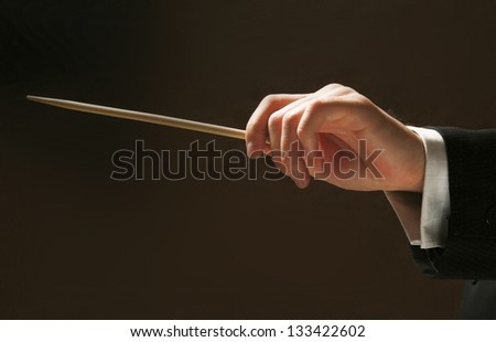 Concert conductor's hands with a baton isolated on a black background - stock photo