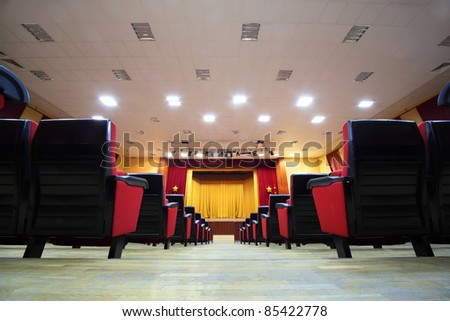 Concert hall and empty stage, many rows of red seats and stage with yellow curtain; view from floor - stock photo