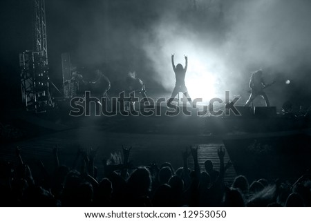 Concert: silhouette of rock singer in front of ecstatic crowd - stock photo
