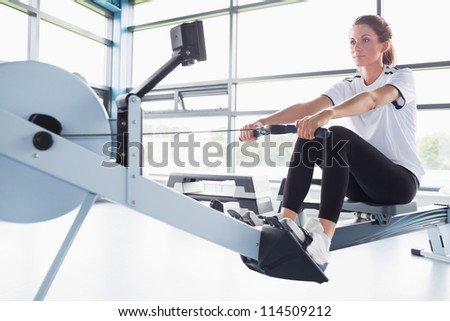 Concetrating woman training on row machine in gym - stock photo