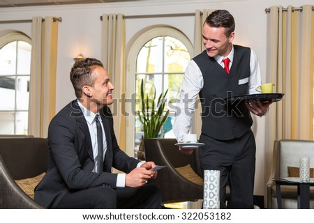Concierge or waiter serving guest at hotel a cup of coffee  - stock photo