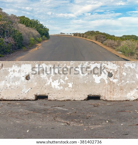 Concrete barrier blocking the uphill road. Rough texture stone block. Bushes, sky and clouds in blurred background. Broken sticks and leaves in foreground.   - stock photo