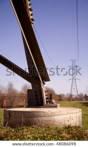 Concrete Base of Electricity Tower Bringing Power To Homes - stock photo