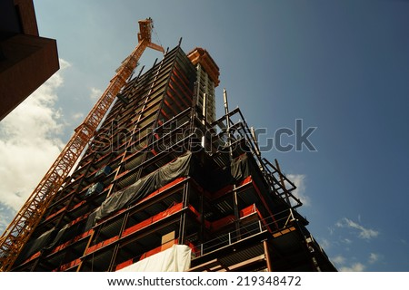 concrete building construction with crane - stock photo