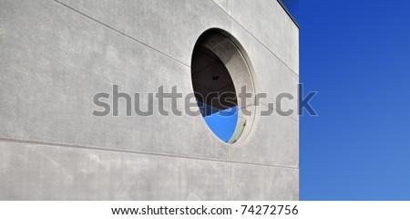 concrete building, round window, blue sky - stock photo