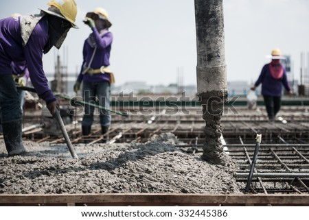 concrete casting work. using a concrete pump machine to fill the floor concrete with worker. selection focus to tube - stock photo