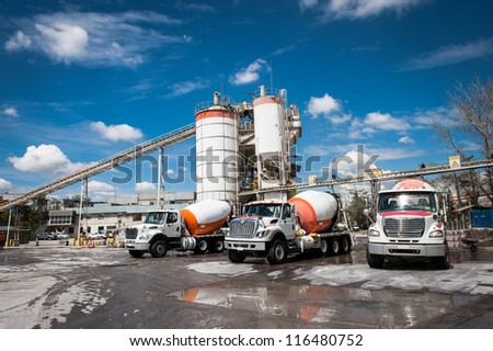 Concrete company and three mixer trucks in a blue sky day. - stock photo