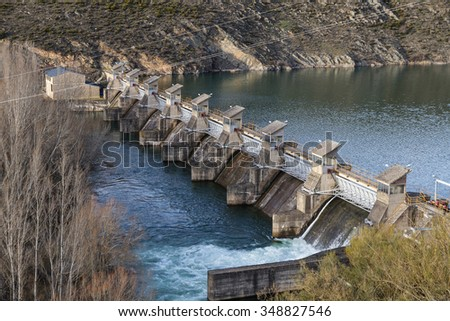 Concrete dam with metal gates containing water in dam, swamp or reservoir, distribution of water for irrigation - stock photo