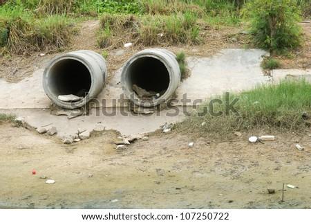Concrete drain pipe, polluting to river - stock photo