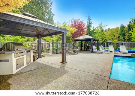 Concrete floor patio area with barbeque, table set, sun chairs and swimming pool - stock photo