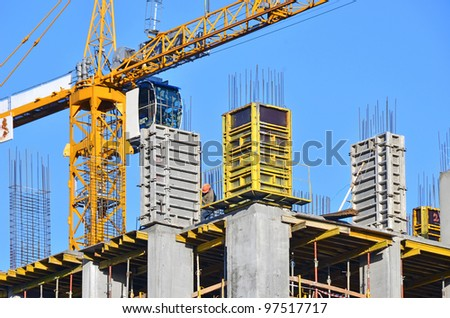 Concrete formwork and crane on construction site - stock photo