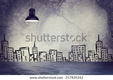 Concrete gray wall with sketches of buildings. Left standing lampshade with directional light