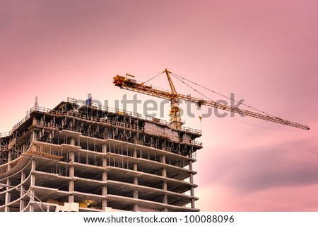 Concrete high rise construction site with a crane on the top. Beautiful sunset sky. - stock photo