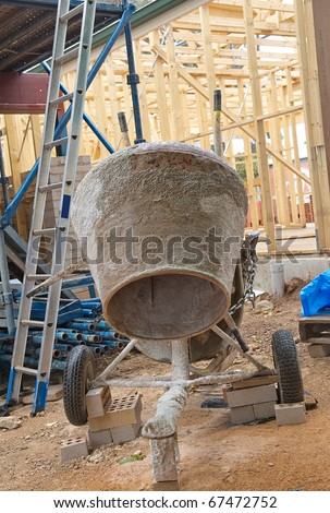 concrete mixer at  new residential construction home framing - stock photo