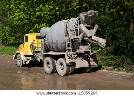 concrete mixer with yellow cab over trees - stock photo