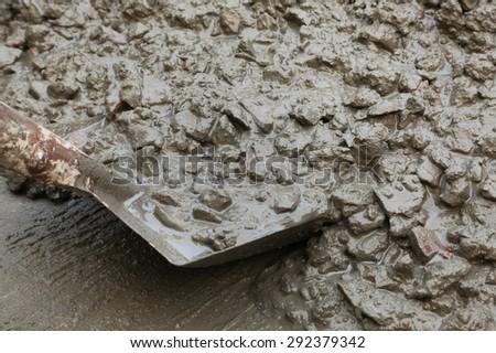 Concrete mixture with shovel for construction - stock photo